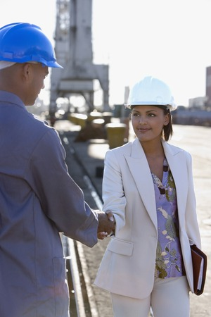 Afro-Amerikaanse zakenvrouw en bouwvakker handen schudden Stockfoto