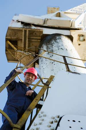 scaling ladder: Asian male construction worker on crane LANG_EVOIMAGES