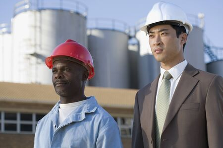 Multi-ethnic businessman and construction worker wearing hardhats