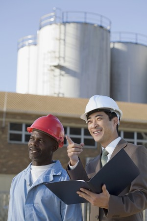 Multi-ethnic businessman and construction worker pointing