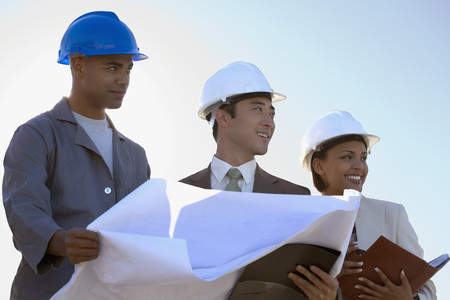 executive helmet: Multi-ethnic businesspeople and construction worker with blueprints