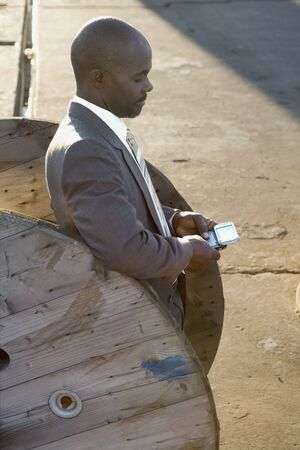 lobbying: African American businessman dialing cell phone LANG_EVOIMAGES