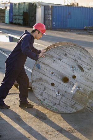swaying: Asian male manual worker pushing wooden spool LANG_EVOIMAGES