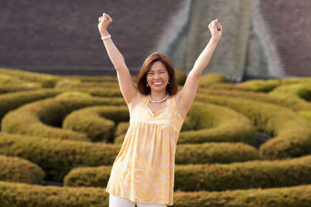 mischeif: Asian woman with arms raised LANG_EVOIMAGES