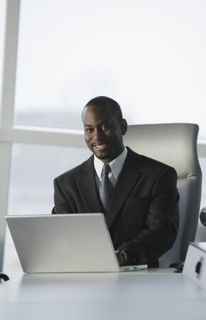 acknowledging: African American businessman typing on laptop