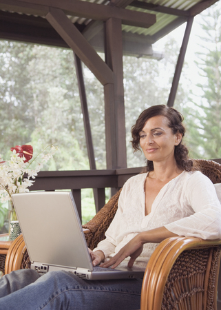 Mature woman typing on laptop Stock Photo