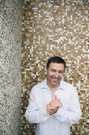 searcher: Hispanic man in front of tile wall