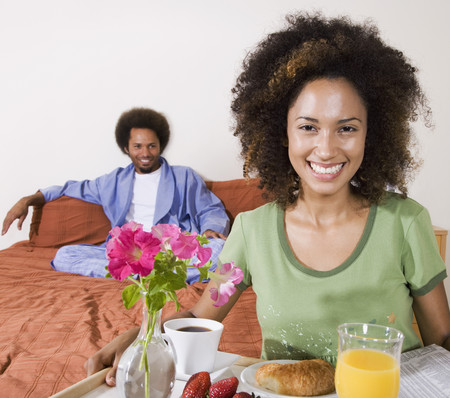 mate married: African woman carrying breakfast in bed tray LANG_EVOIMAGES