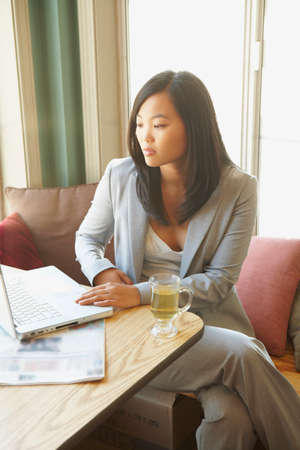 telecommuter: Asian businesswoman looking at laptop
