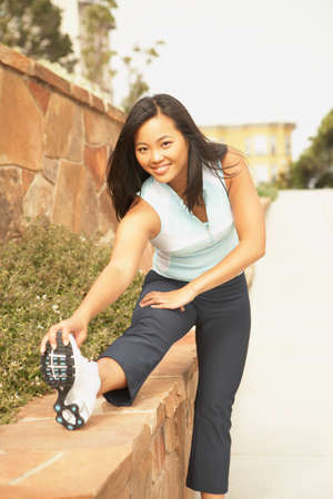 german ethnicity: Asian woman in running gear stretching