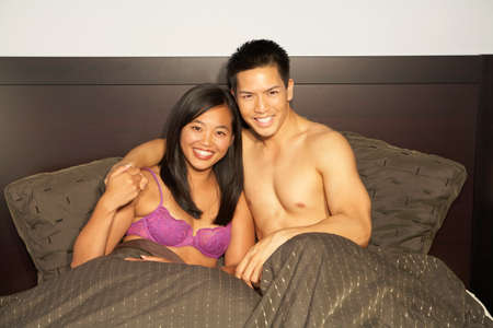 Asian couple sitting in bed