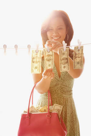 dollarbill: Asian woman hanging money on clothes line