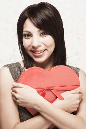 mischeif: Hispanic woman hugging heart-shaped box