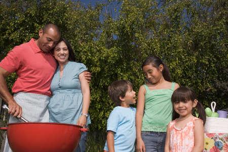 relishing: Hispanic family barbequing LANG_EVOIMAGES