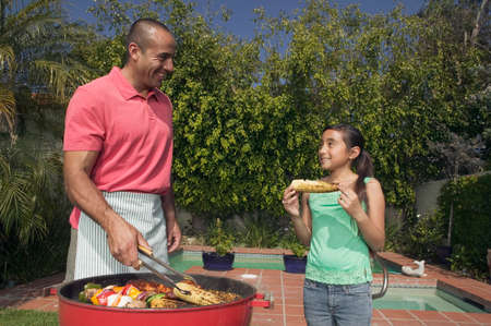 Hispanic father and daughter barbequing Stock Photo