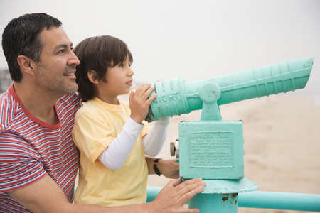shopping buddies: Hispanic father and son with telescope LANG_EVOIMAGES