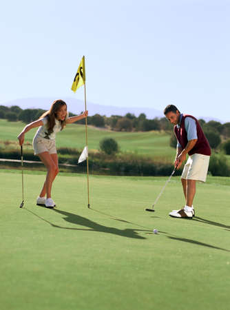 spectating: Couple playing golf