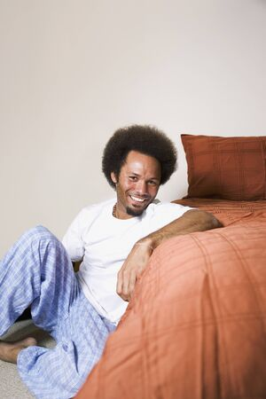 casualness: African man sitting next to bed