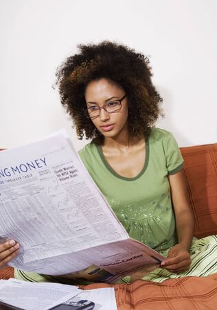 casualness: African woman reading newspaper