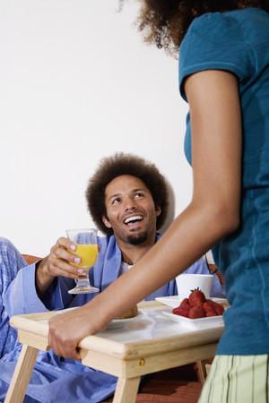 skepticism: African woman bringing breakfast in bed to husband LANG_EVOIMAGES