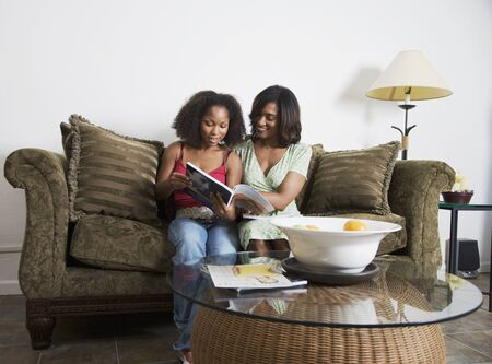 African mother and adult daughter reading magazine