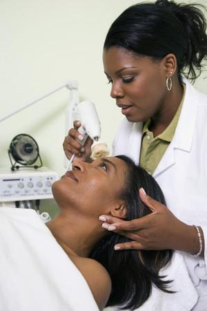 tratamiento facial: Mujer africana de spa que reciben tratamiento facial