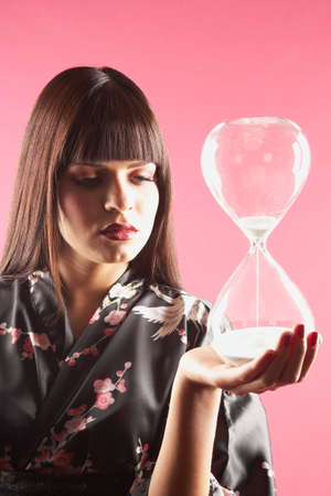 spectating: Middle Eastern woman holding hourglass