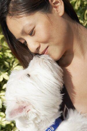 motioning: Asian woman kissing dog