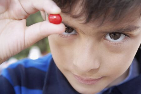 possessive: Hispanic boy holding piece of candy LANG_EVOIMAGES