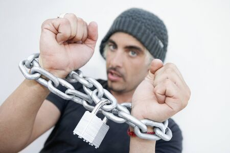 ceasing: Hispanic man with chains around wrists LANG_EVOIMAGES