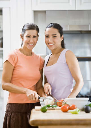 mischeif: Hispanic women chopping vegetables