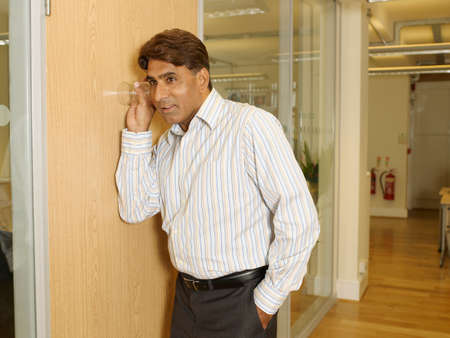 conferring: Indian businessman listening through wall with glass LANG_EVOIMAGES
