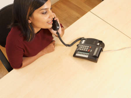 conferring: Indian businesswoman talking on telephone
