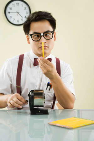 unfashionable: Nerdy Asian man sharpening pencil LANG_EVOIMAGES