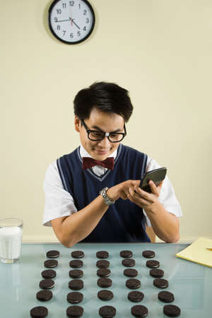 exactitude: Nerdy Asian man counting cookies