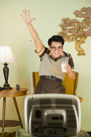 gusto: Nerdy Asian man cheering in front of television