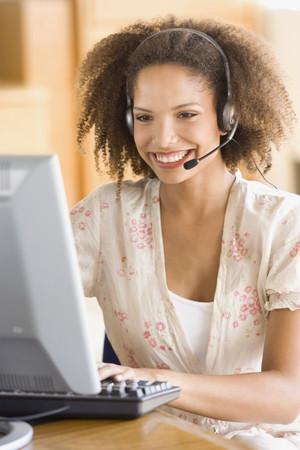 telecommuter: African businesswoman wearing headset LANG_EVOIMAGES