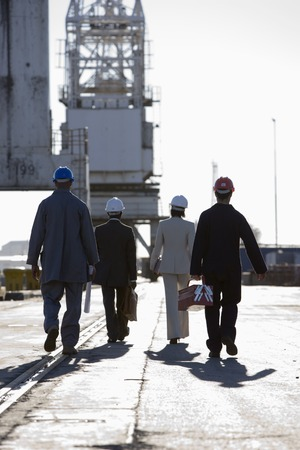 drydock: Multi-ethnic businesspeople and construction workers walking