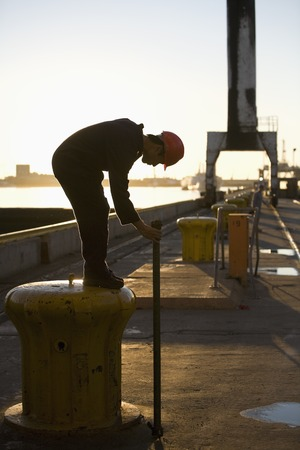 profile measurement: Asian male dock worker holding pipe