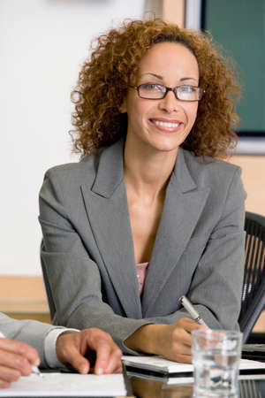 exerting: African businesswoman sitting at table