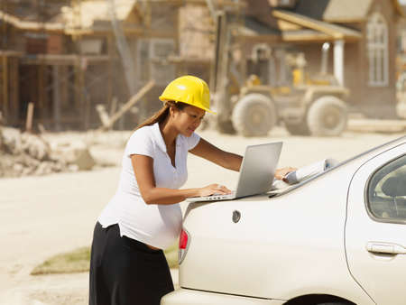 sweatsuit: Pregnant Asian businesswoman with laptop at construction site