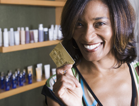 irish ethnicity: African woman holding credit card LANG_EVOIMAGES