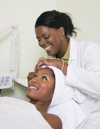 indulging: African woman receiving spa facial treatment LANG_EVOIMAGES