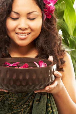 pacific islander: Pacific Islander woman holding spa treatment bowl
