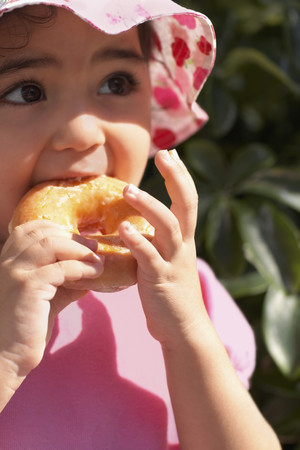seriousness skill: Hispanic baby girl eating doughnut