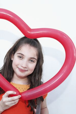 adoring: Hispanic girl holding heart-shaped balloon