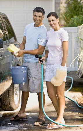 washing car: Multi-ethnic couple washing car LANG_EVOIMAGES
