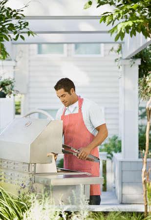 mischeif: Hispanic man next to barbecue