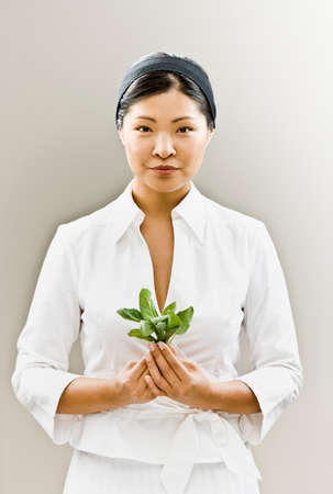 attired: Asian woman holding flower