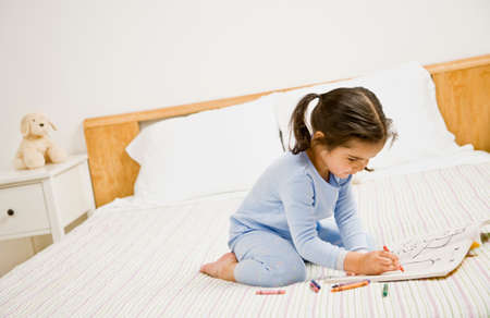 only one girl: Mixed Race girl coloring on bed